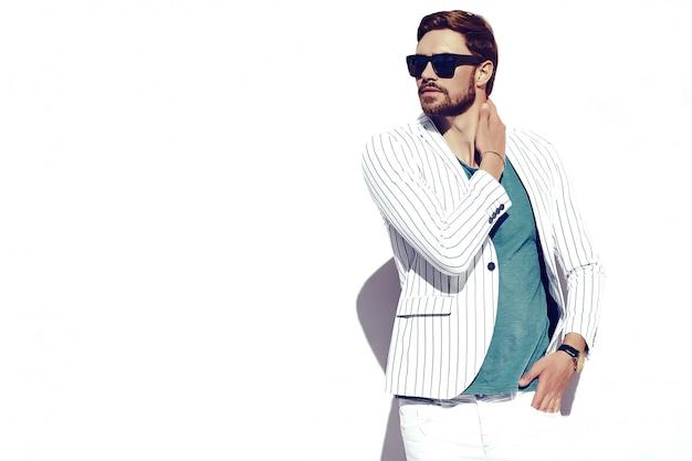 Joven elegante confiado feliz apuesto hombre de negocios modelo en traje de estilo de vida en la calle de pie cerca de la pared