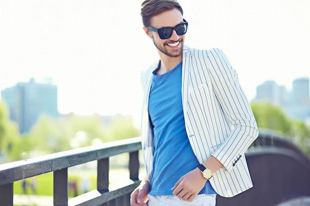 Joven elegante confiado feliz apuesto hombre de negocios modelo en traje hipster estilo de vida de tela en la calle junto a la pared