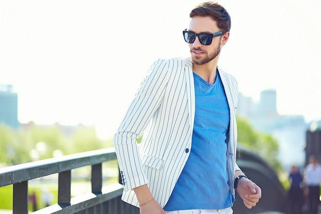 Joven elegante confiado feliz apuesto hombre de negocios modelo en traje hipster estilo de vida de tela en la calle