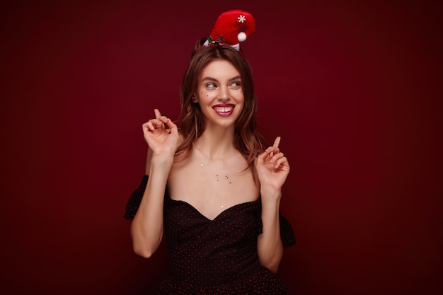 Joven y elegante dama alegre con maquillaje de noche levantando los dedos índices y sonriendo felizmente, disfrutando de la mascarada de la fiesta temática de navidad mientras posa