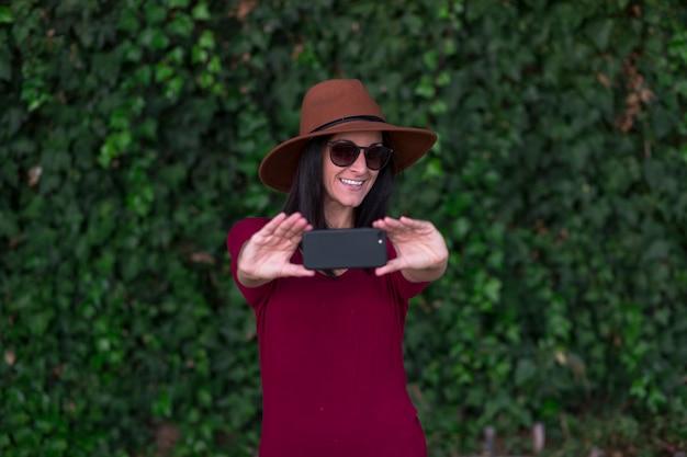 Joven elegante haciendo selfie sobre hiedra verde deja fondo, vistiendo elegante sombrero marrón, camiseta roja y gafas de sol, haciendo selfie y divirtiéndose.