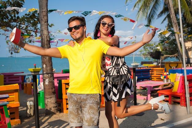 Joven elegante hipster hermosa pareja en vacaciones de verano en tailandia, coqueta, atuendo de moda, gafas de sol, romance tropical, sonriente, feliz, escuchando música, humor de fiesta, café en la playa