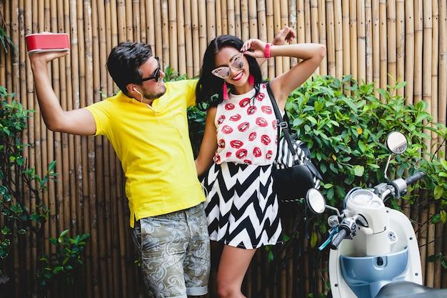 Joven elegante hipster hermosa pareja en vacaciones de verano en tailandia, coqueta, traje de tendencia de moda, gafas de sol, vacaciones tropicales, romance de vacaciones, sonriente, feliz, escuchando música, fiesta, baile