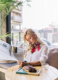 Joven elegante mujer leyendo el periódico en la cafetería