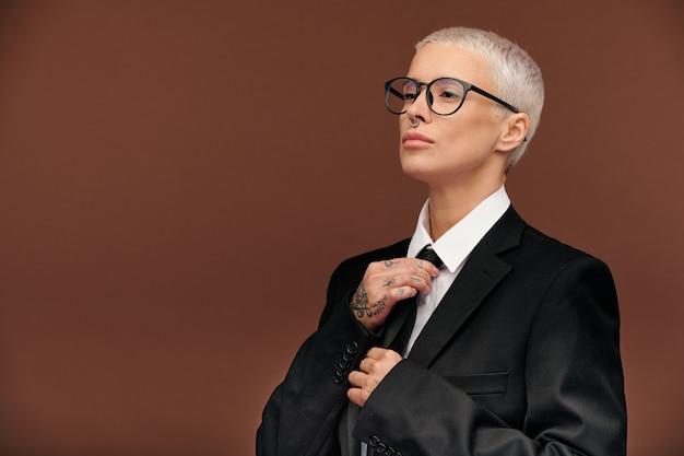 Joven elegante mujer masculina con cabello rubio teñido corto atando una corbata negra mientras se viste para el trabajo o evento formal de forma aislada