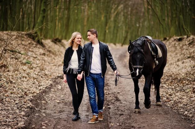 Joven elegante pareja de enamorados caminando con caballo en el bosque de otoño
