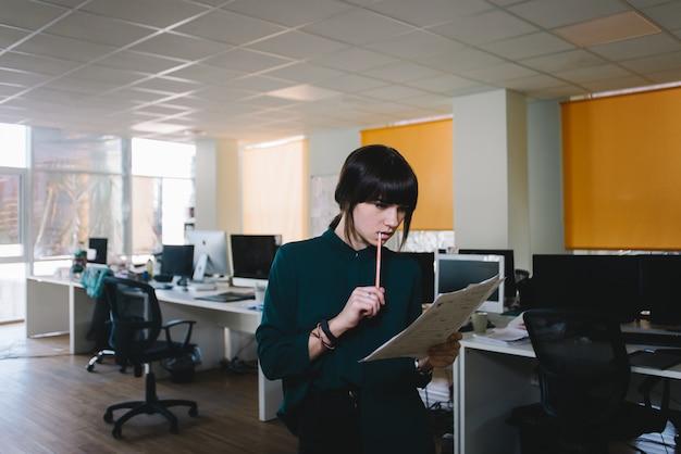 La joven y elegante secretaria revisa los papeles. contra el telón de fondo de una hermosa oficina.