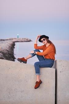 Joven elegante sentado en un puerto marítimo