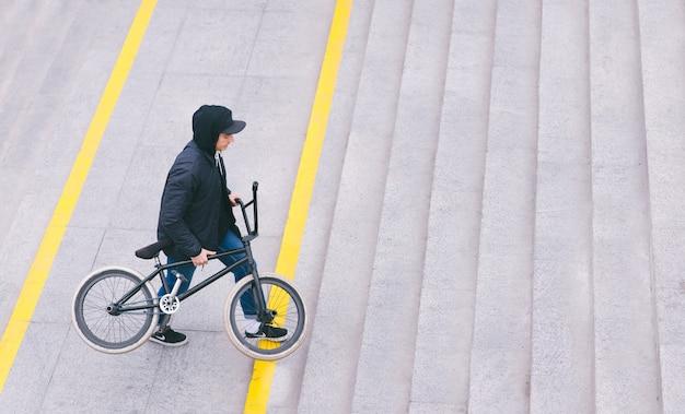 Un joven elegante sube una escalera con bmx en bicicleta en sus manos. camina con una bicicleta. concepto de bmx. cultura callejera