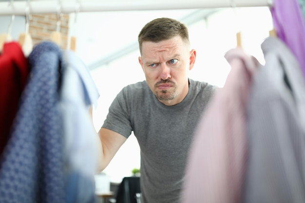 Joven elegir camisa en primer plano de armario