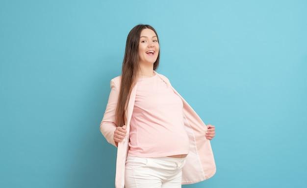 Joven embarazada aislada en azul
