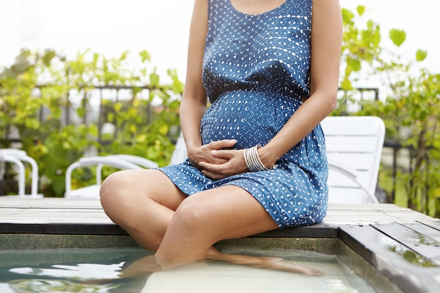Joven embarazada bronceada sentada en el borde de la piscina con las piernas cruzadas y sumergida en el agua, manteniendo las manos en la barriga, disfrutando de momentos felices y pacíficos de su embarazo al aire libre