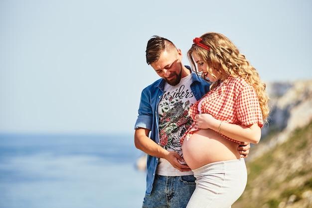 Joven embarazada caminando con su marido contra vistas al mar