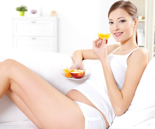 Joven embarazada comiendo frutas frescas en casa