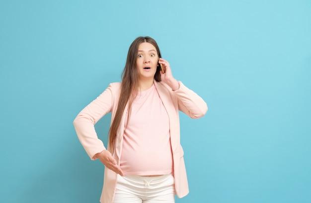 Joven embarazada hablando por teléfono