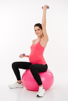 Joven embarazada haciendo ejercicio con pelota de fitness y pesas