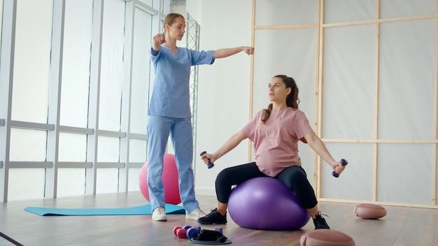 Una joven embarazada está haciendo ejercicios con un trabajador de la salud en una clínica.