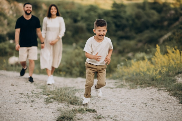 Joven embarazada con marido e hijo en un bosque