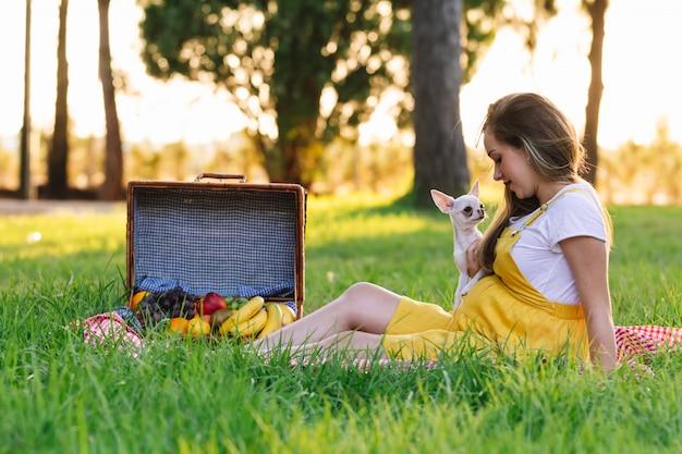 Joven embarazada en un picnic al atardecer. con perro chihuahua