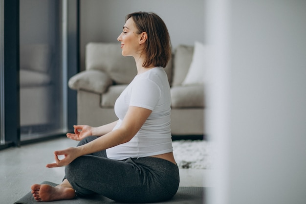 Joven embarazada practicando yoga en casa