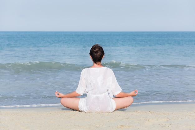Joven embarazada practicando yoga en el mar