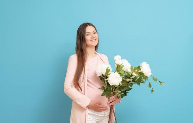 Joven embarazada con un ramo de flores