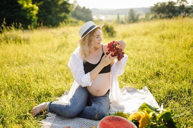 Joven embarazada relajándose en el parque al aire libre y comiendo sandía, embarazo saludable