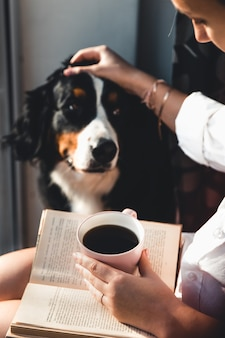 Joven embarazada sentada en la sala de estar con su lindo perro, leyendo y tomando café