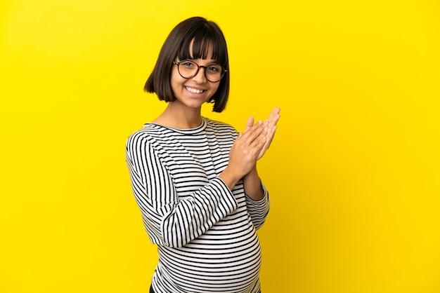 Joven embarazada sobre fondo amarillo aislado aplaudiendo
