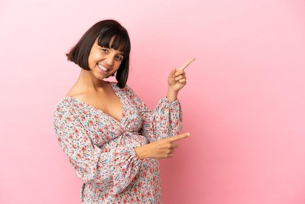 Joven embarazada sobre fondo rosa aislado apuntando con el dedo hacia un lado y presentando un producto