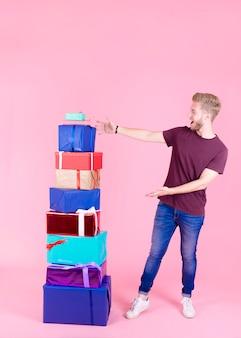 Joven emocionado mostrando pila de coloridos regalos contra el fondo rosa