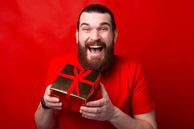 Un joven está emocionado sosteniendo un regalo recibido.