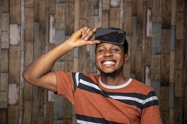 Joven emocionado por su teléfono mientras lo sostiene contra su cabeza