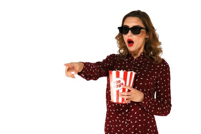 Joven emocional con palomitas viendo la película de acción en gafas 3d