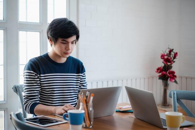 Joven empleado asiático en ropa casual escribiendo en la computadora durante el día de trabajo en la oficina en casa