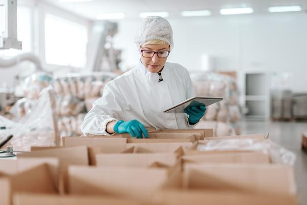 Joven empleado caucásico en uniforme estéril con tableta y contando productos en cajas. interior de la fábrica de alimentos.