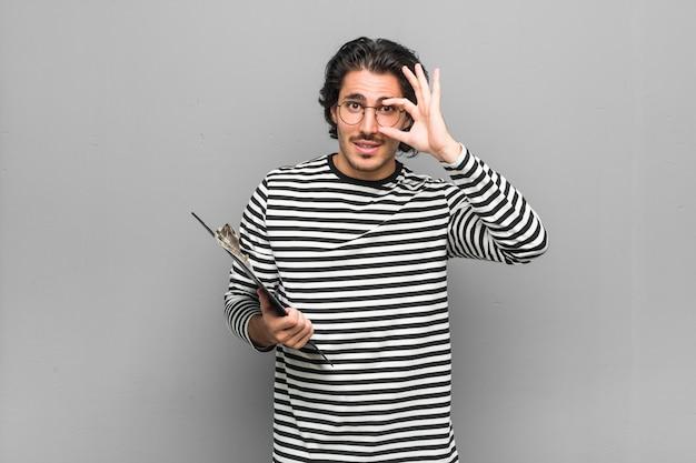 Joven empleado hombre sosteniendo un inventario que muestra bien firmar sobre los ojos