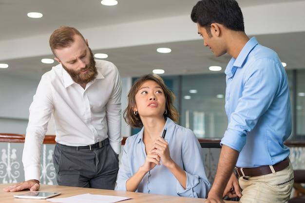 Joven empleado pidiendo ayuda a sus colegas.