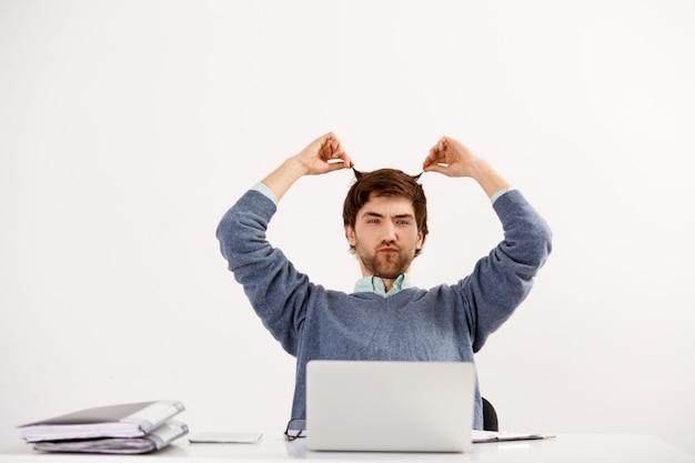 Joven empleado trabajando con la computadora portátil en el escritorio de la oficina, haciendo muecas y tocando el cabello, postergando