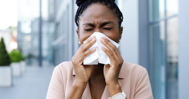 Joven empresaria afroamericana enferma toser y estornudar en la servilleta al aire libre. mujer enferma con síntoma de coronavirus en la calle cerca del centro de negocios. mujer malsana estornuda y tose. concepto covid.