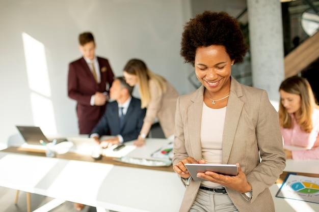 Joven empresaria afroamericana de pie y con tableta digital en la oficina moderna