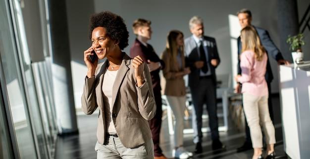 Joven empresaria afroamericana de pie y mediante teléfono móvil en la oficina moderna