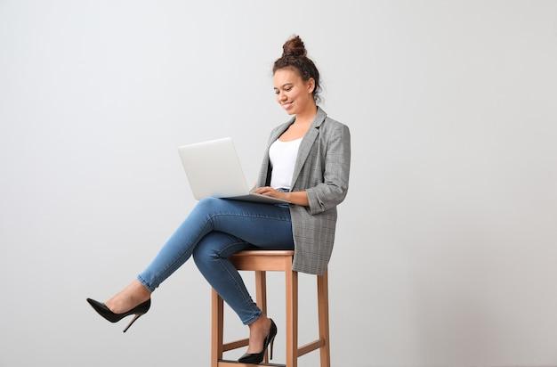 Joven empresaria afroamericana con portátil sentado en una silla junto a la pared gris
