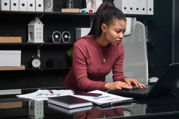 Joven empresaria afroamericana trabajando en la computadora portátil en la oficina