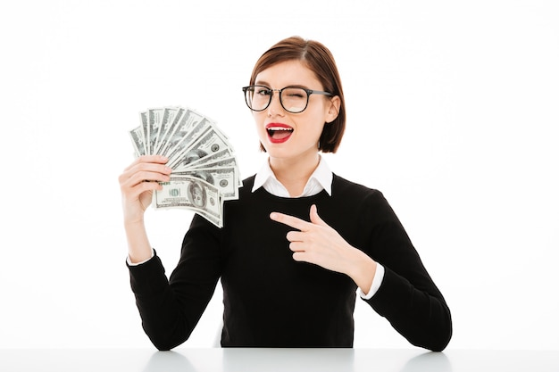 Joven empresaria apuntando con el dedo al dinero y guiñando un ojo