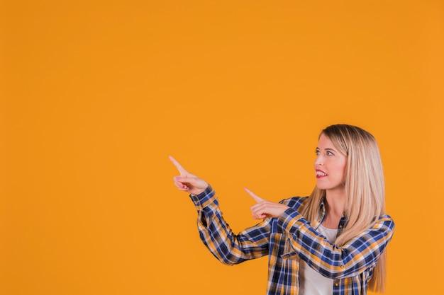 Una joven empresaria apuntando sus dedos contra un fondo naranja