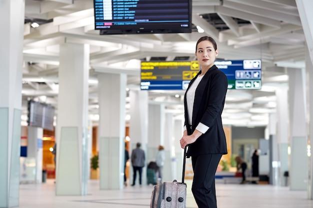 Joven empresaria asiática en el aeropuerto con carro