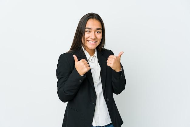 Joven empresaria asiática aislada en la pared blanca levantando ambos pulgares, sonriente y confiada.