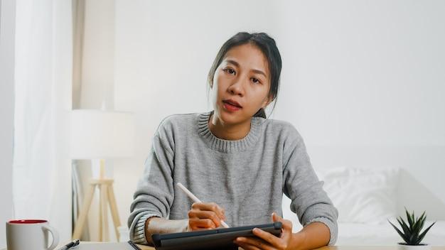 Joven empresaria asiática con computadora portátil hablar con colegas sobre el plan en la reunión de videollamada mientras trabaja desde casa en el dormitorio