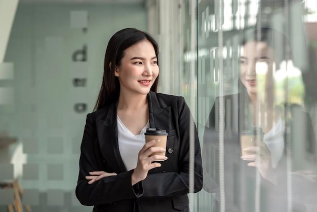 Joven empresaria asiática descansando del trabajo sosteniendo una taza de café en la oficina de cristal.